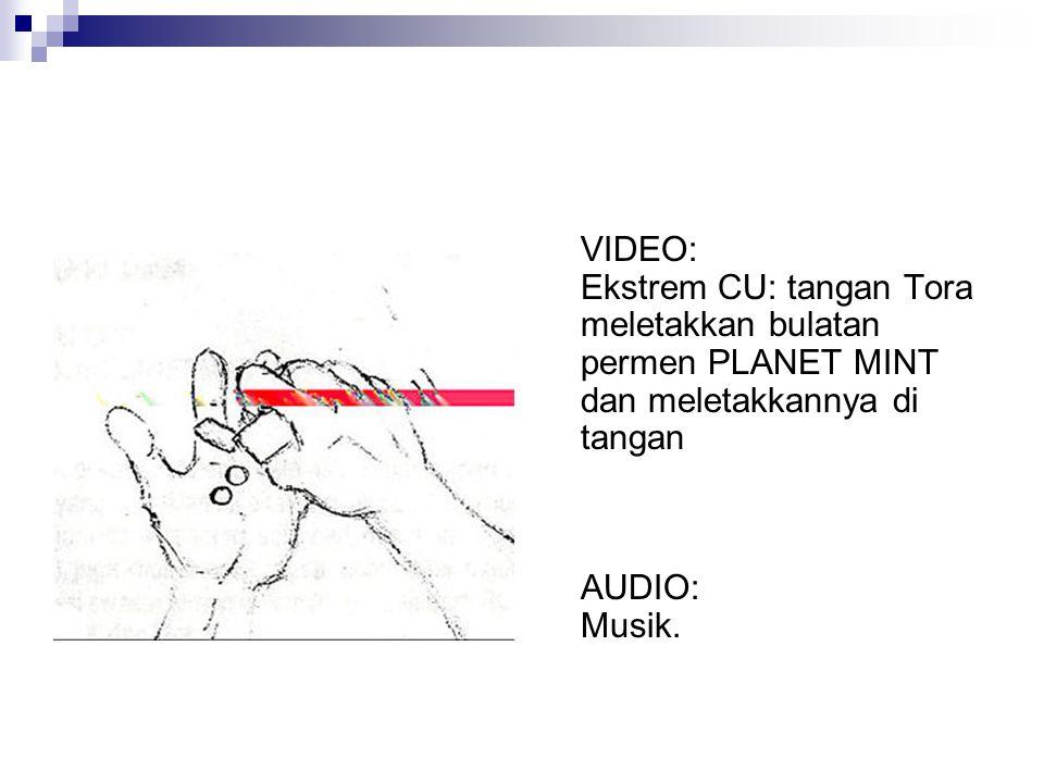 VIDEO: Ekstrem CU: tangan Tora meletakkan bulatan permen PLANET MINT dan meletakkannya di tangan AUDIO: Musik.