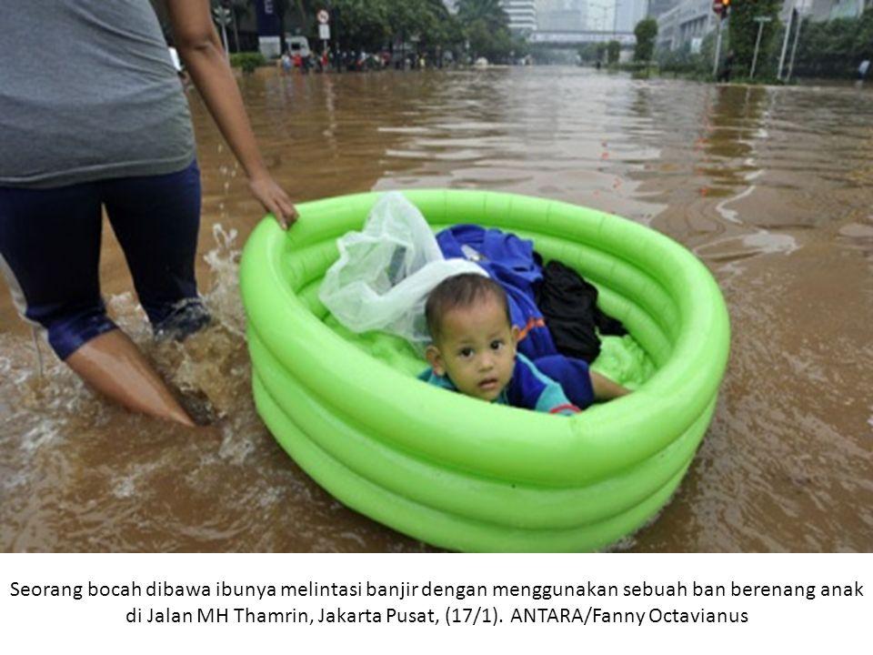 Seorang bocah dibawa ibunya melintasi banjir dengan menggunakan sebuah ban berenang anak di Jalan MH Thamrin, Jakarta Pusat, (17/1).