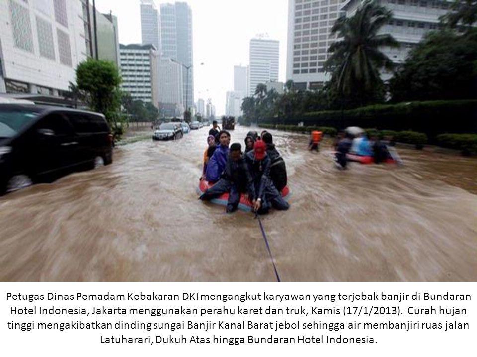 Petugas Dinas Pemadam Kebakaran DKI mengangkut karyawan yang terjebak banjir di Bundaran Hotel Indonesia, Jakarta menggunakan perahu karet dan truk, K