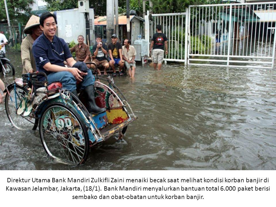 Direktur Utama Bank Mandiri Zulkifli Zaini menaiki becak saat melihat kondisi korban banjir di Kawasan Jelambar, Jakarta, (18/1).