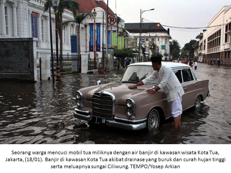 Seorang warga mencuci mobil tua miliknya dengan air banjir di kawasan wisata Kota Tua, Jakarta, (18/01).