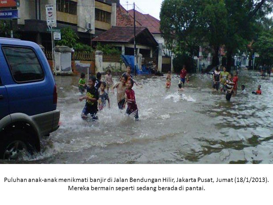 Puluhan anak-anak menikmati banjir di Jalan Bendungan Hilir, Jakarta Pusat, Jumat (18/1/2013).