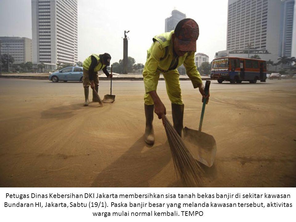 Petugas Dinas Kebersihan DKI Jakarta membersihkan sisa tanah bekas banjir di sekitar kawasan Bundaran HI, Jakarta, Sabtu (19/1).