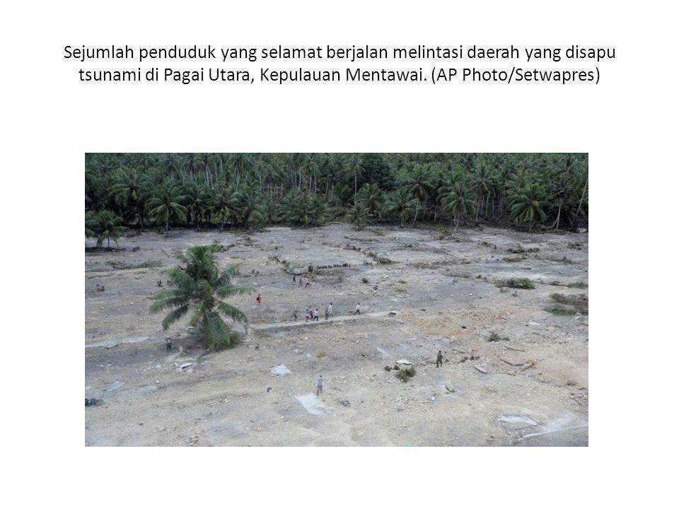 Sejumlah penduduk yang selamat berjalan melintasi daerah yang disapu tsunami di Pagai Utara, Kepulauan Mentawai.