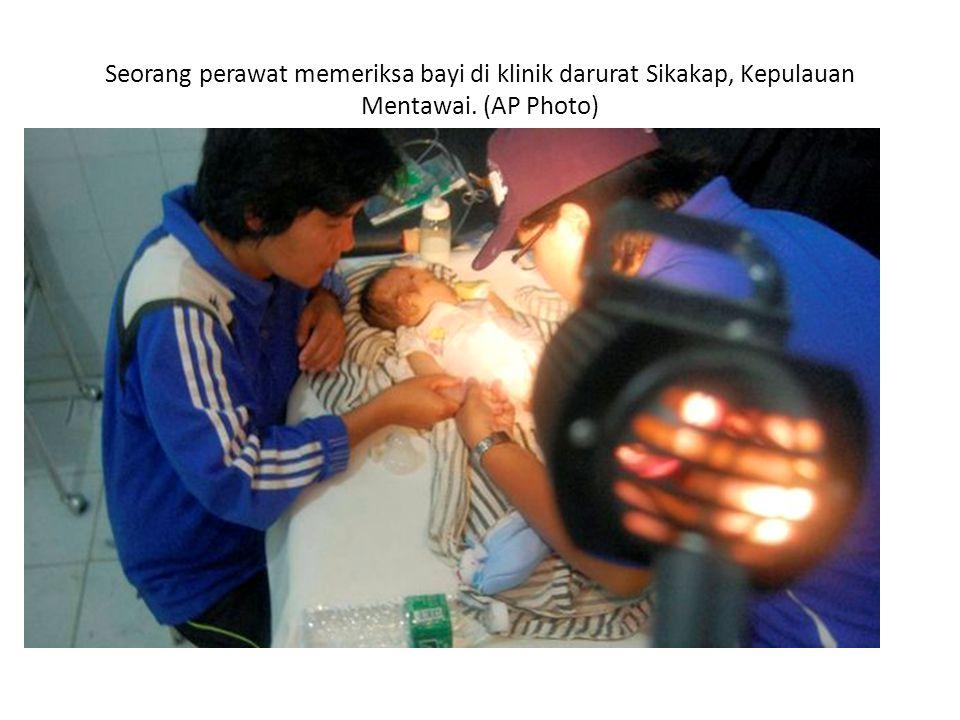 Seorang perawat memeriksa bayi di klinik darurat Sikakap, Kepulauan Mentawai. (AP Photo)