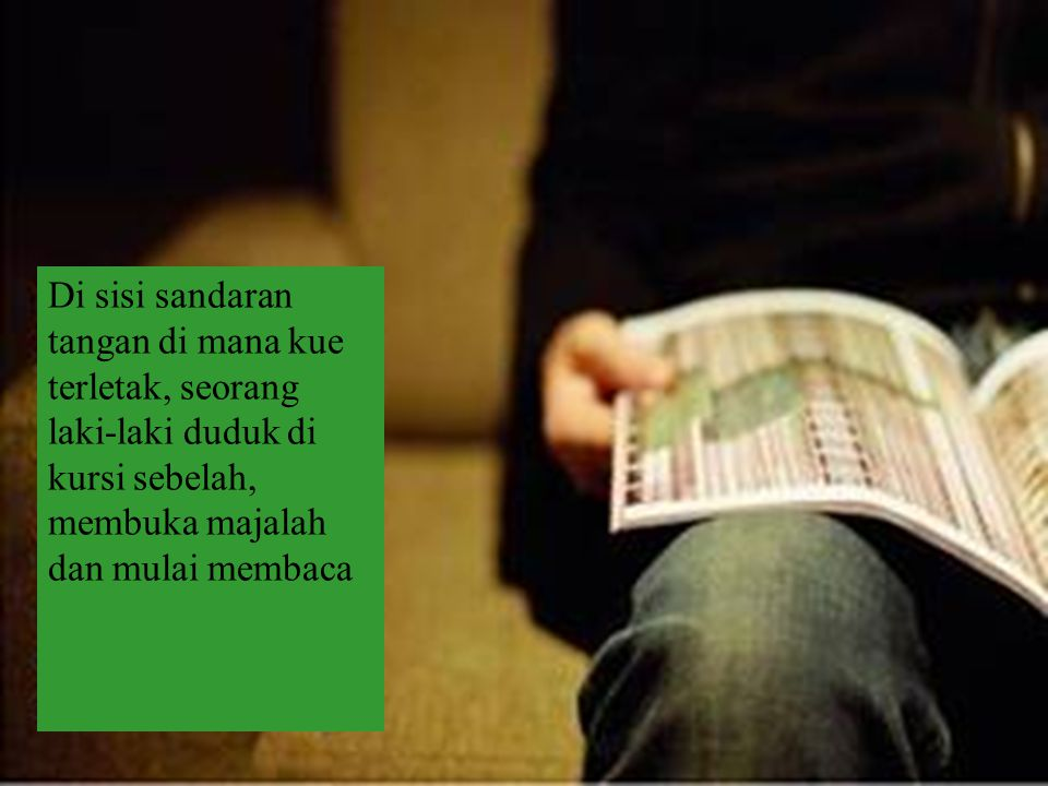 Di sisi sandaran tangan di mana kue terletak, seorang laki-laki duduk di kursi sebelah, membuka majalah dan mulai membaca