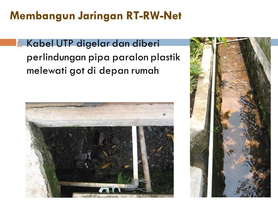 Membangun Jaringan RT-RW-Net  Kabel UTP digelar dan diberi perlindungan pipa paralon plastik melewati got di depan rumah