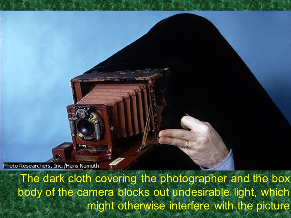 The dark cloth covering the photographer and the box body of the camera blocks out undesirable light, which might otherwise interfere with the picture